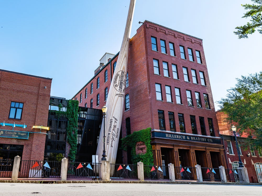 a large wooden bat in louisville leans against a red brick factory