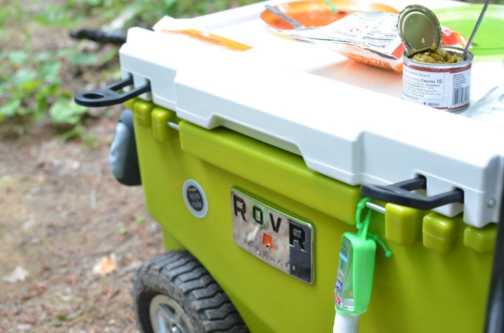 a rovr cooler with food on top and hand gel attached