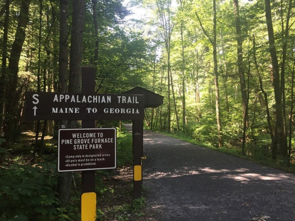 a wooden sign on the PA appalachian trail pointing at maine and georgia