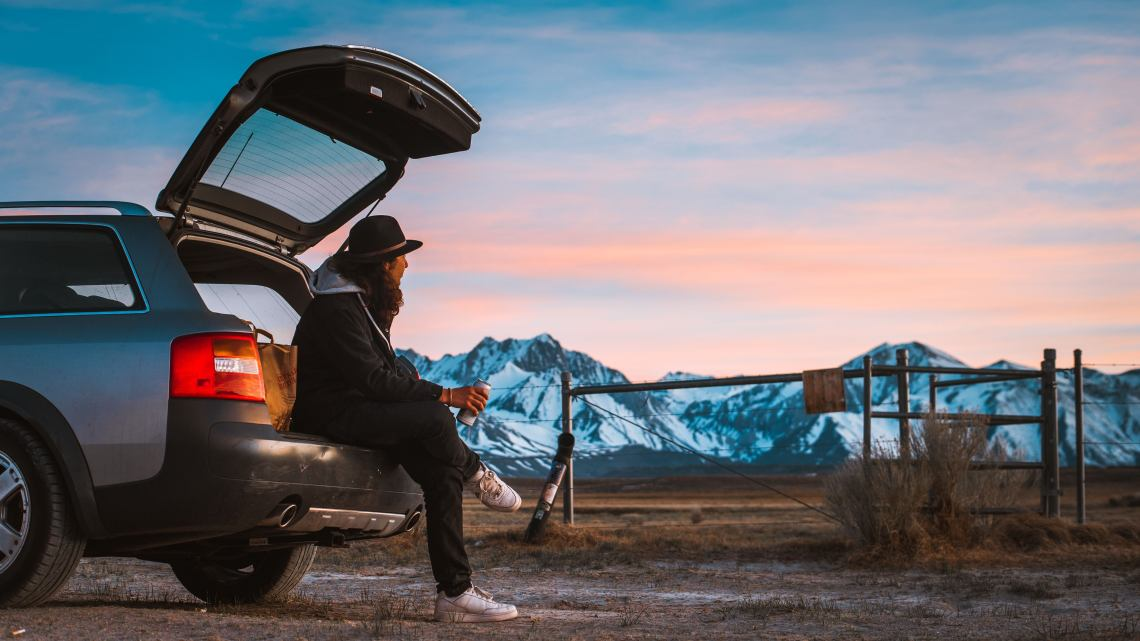 man rests on back bumper of his car with a beer while watching alpine sunset