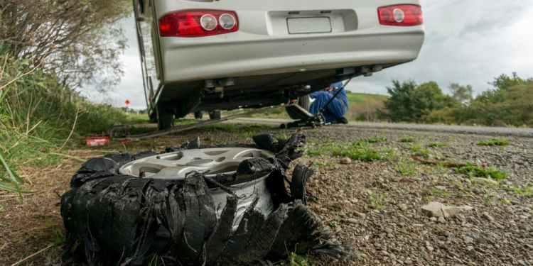 a man fixing an RV camper next to a broken tire