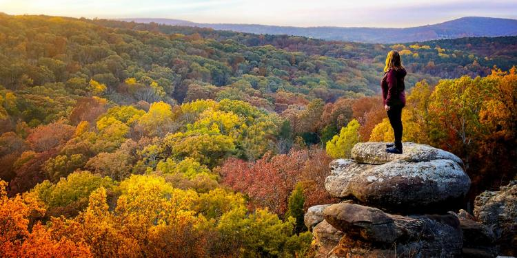 Woman standing on cliffs at garden of gods overlooking Shawnee National Forest.