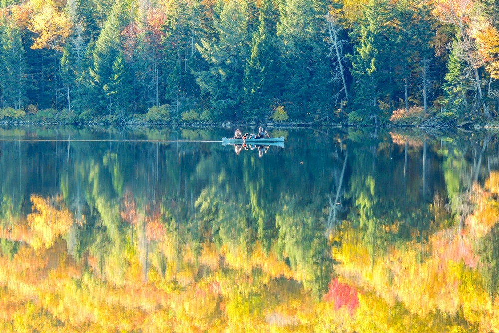 People in canoe on river with reflection of yellow trees