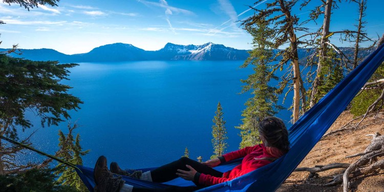 a woman resting in a hammock over crater lake in oregon