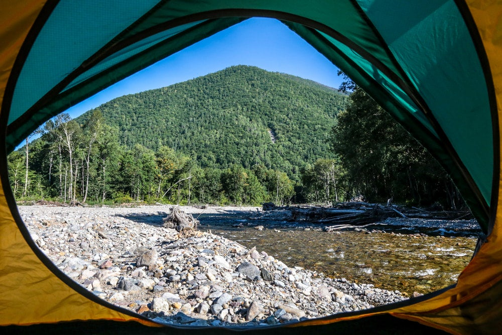 a green mountain, rocky riverbed and shallow river as seen through the door of a green tent