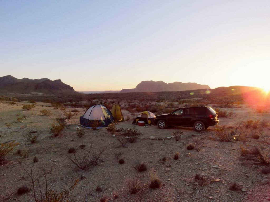 Tent pitched beside car in sandy desert.