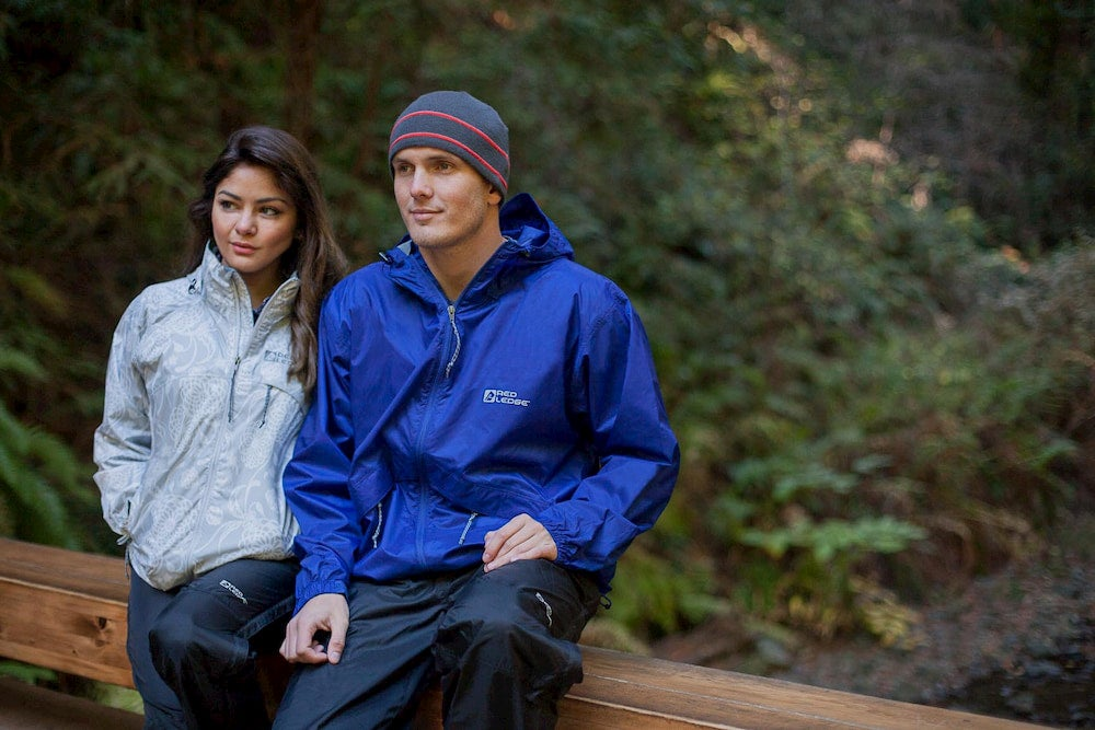 Man and woman wearing jackets and sitting on bridge in a forest