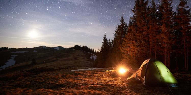 long exposure of beach campsite featuring green tent and bright campfire