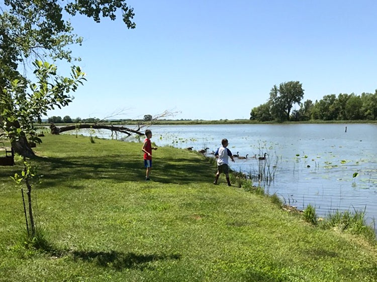 two kids playing near water at lewis and clark state park iowa
