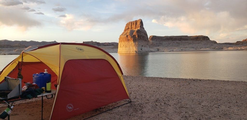 a canopy tent hanging over a campsite on the shore of a lake in utah