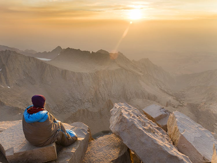 hiker on mount whitney summit at sunrise