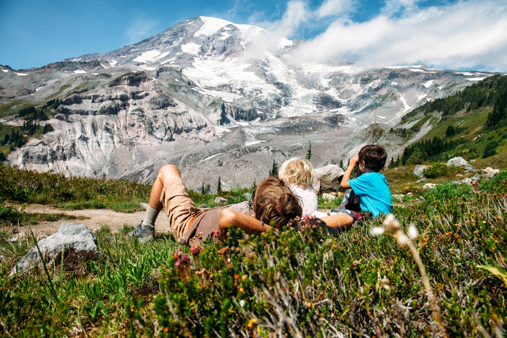 Father and kids laying in flowers with Mount Ranier in background