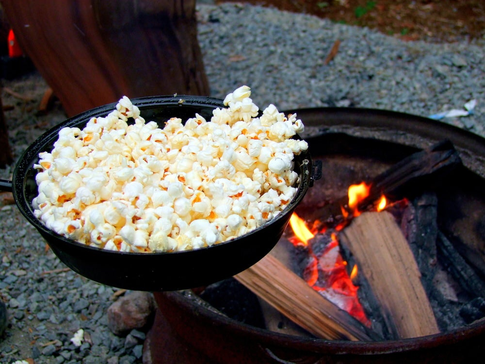 popcorn cooking over a campfire in a cast iron