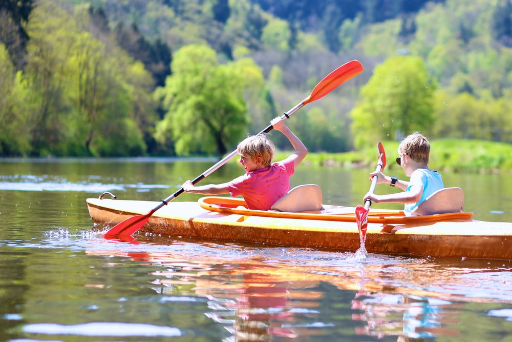two children in a kayak on a river