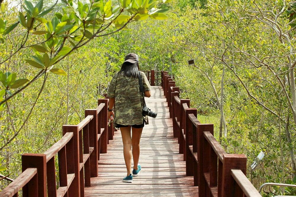 Woman walking on bridge holding camera