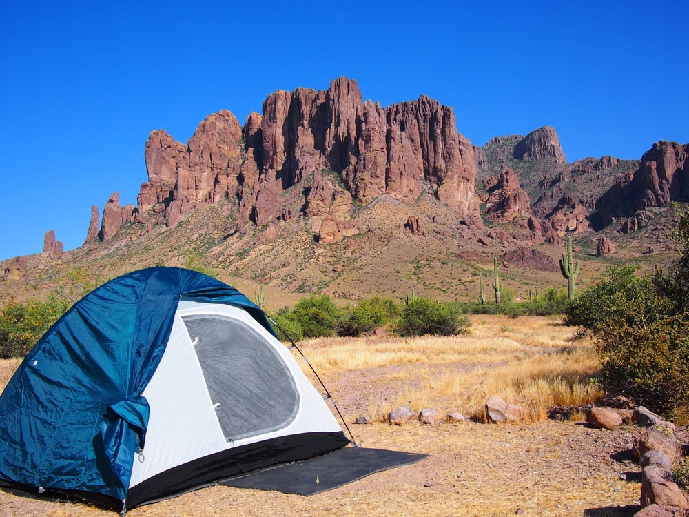 Tent in foreground with red rock formation in background