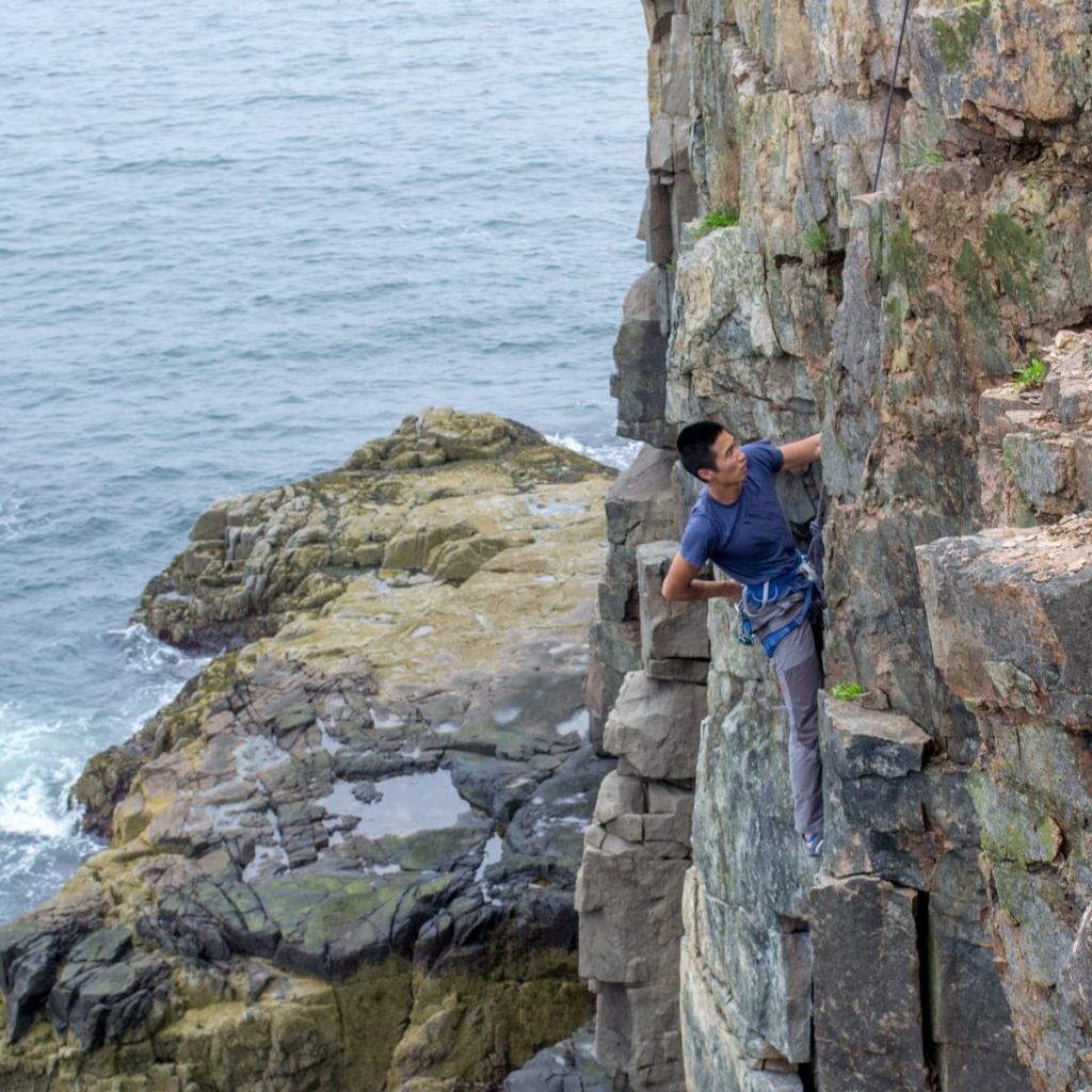 a man paused on a rock wall climbing in acadia national park