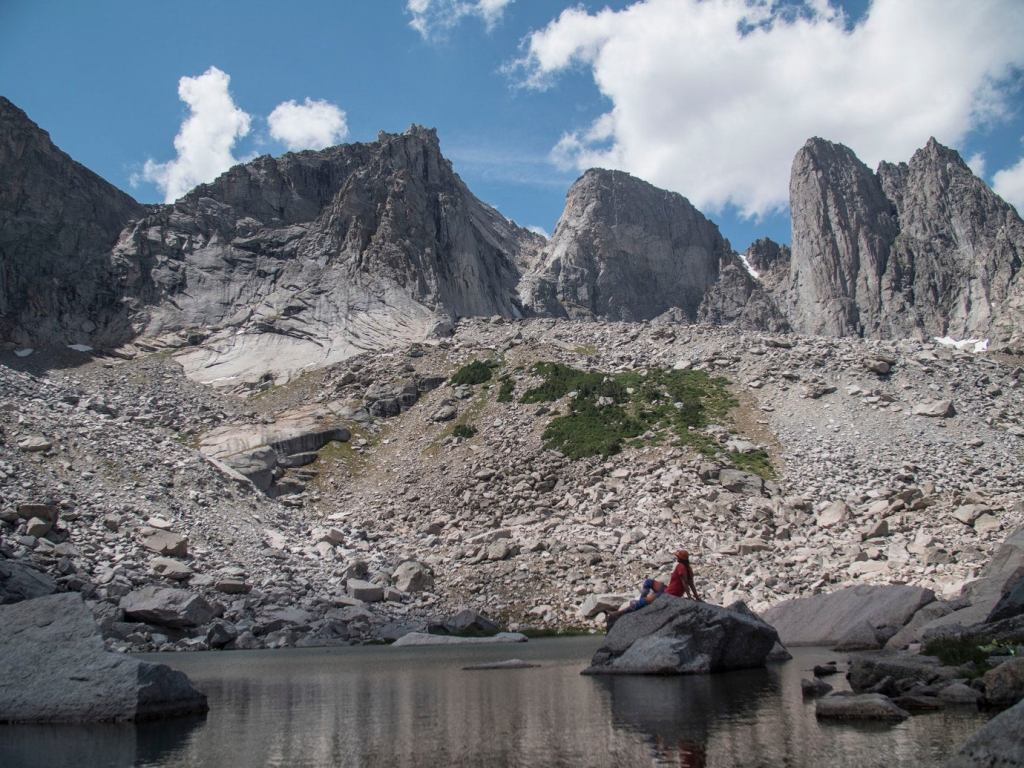 a man sits ona . rock in a lake beneath grey mountains in backcountry wyoming