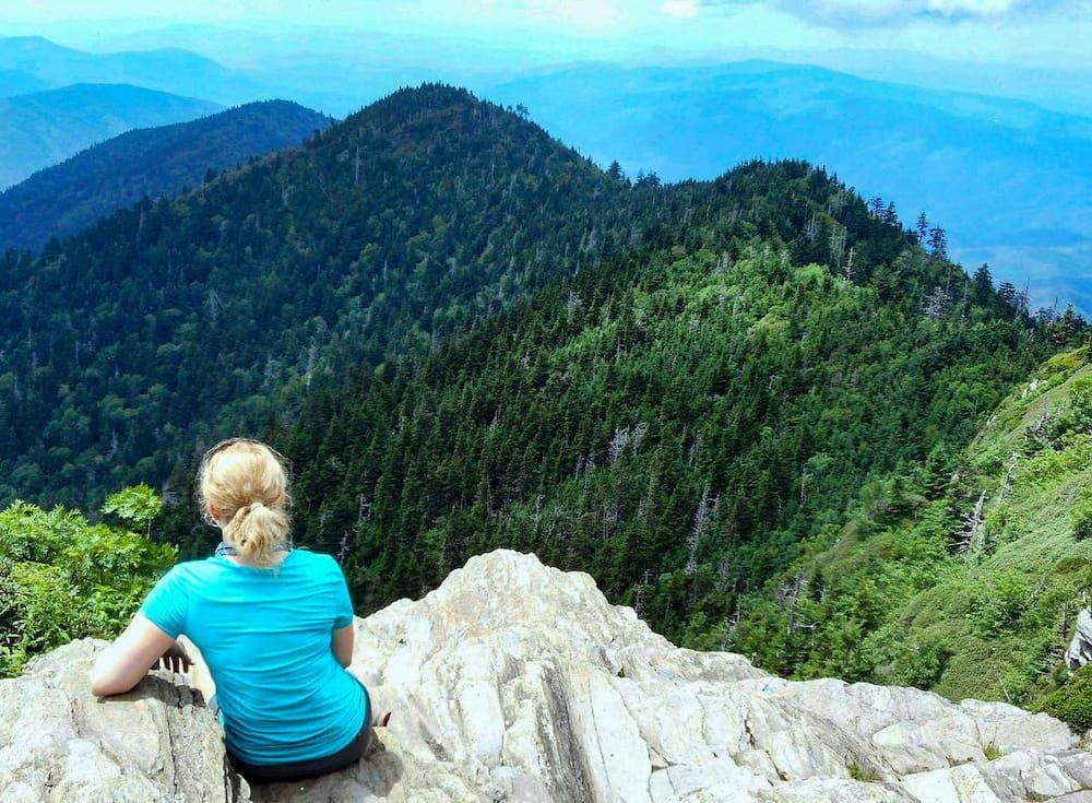 Woman sitting on rocks overlooking mountains