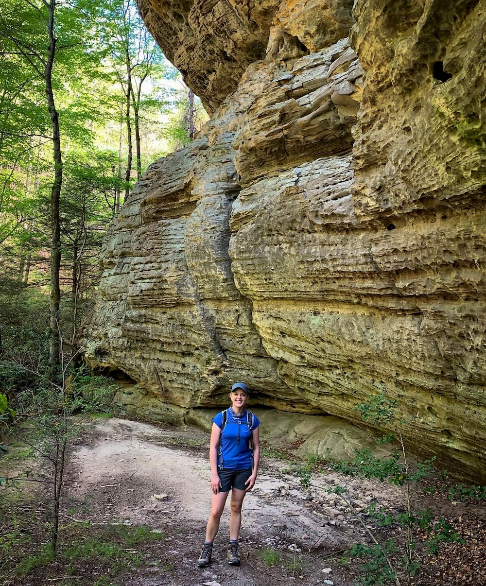 Woman standing next to rocks with forest in background