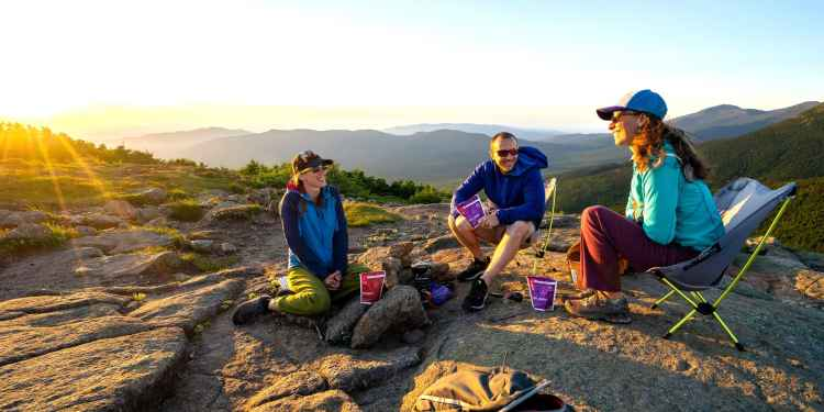 three people sitting on a rock face eating goot to go camping meals