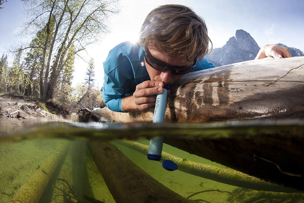 a man sucking water from a river through a straw