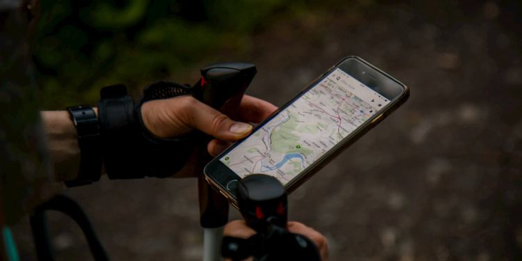 Hiker using trekking poles and hiking app on their smartphone.