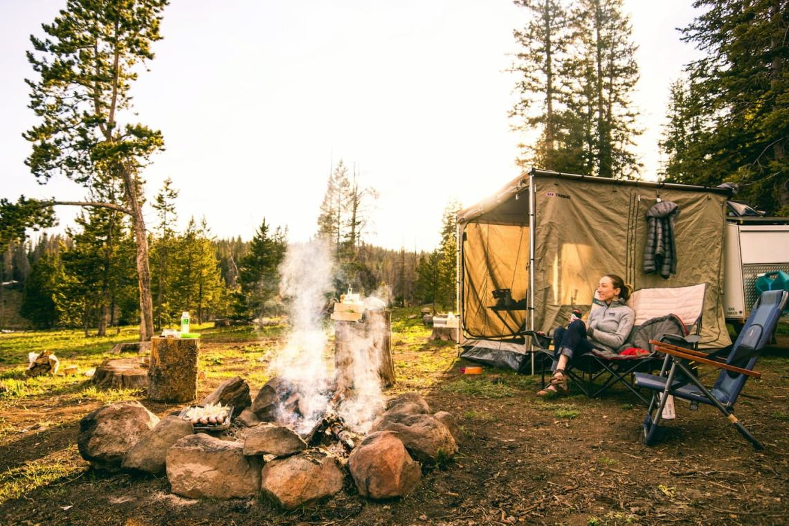 Women lounging beside campfire and tent.