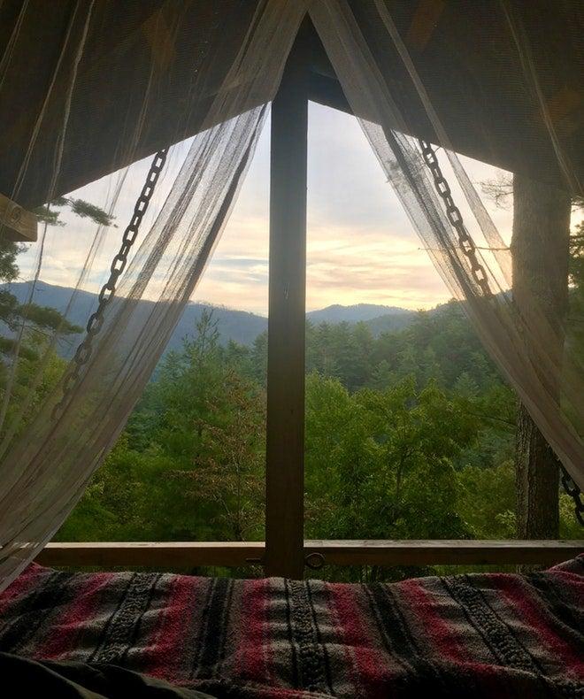 a sunrise through a window in a glamping cabin in north carolina
