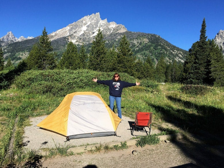 woman poses for photo with arms outstretched at Jenny Lake Campground in wyoming, photo from a camper on The Dyrt