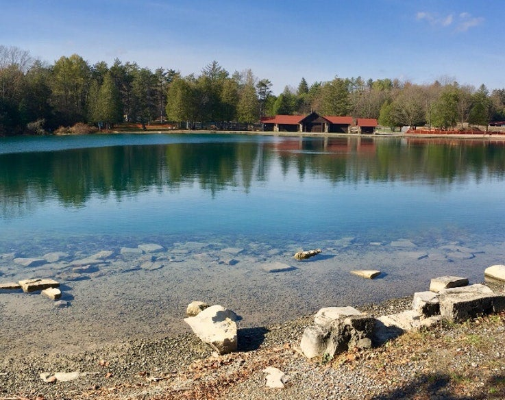lodge visible across a calm Green Lake in New York state park, photo from a camper on The Dyrt