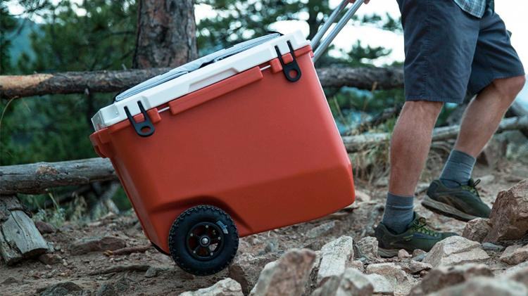 a man tows a rolling cooler on a trail