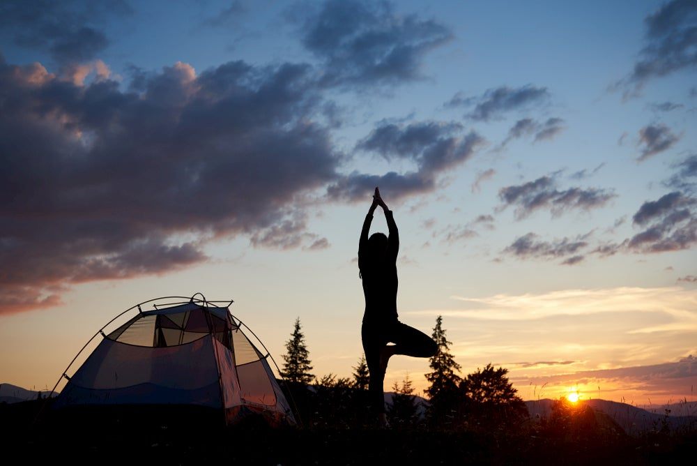 Person doing yoga during dusk beside their tent.