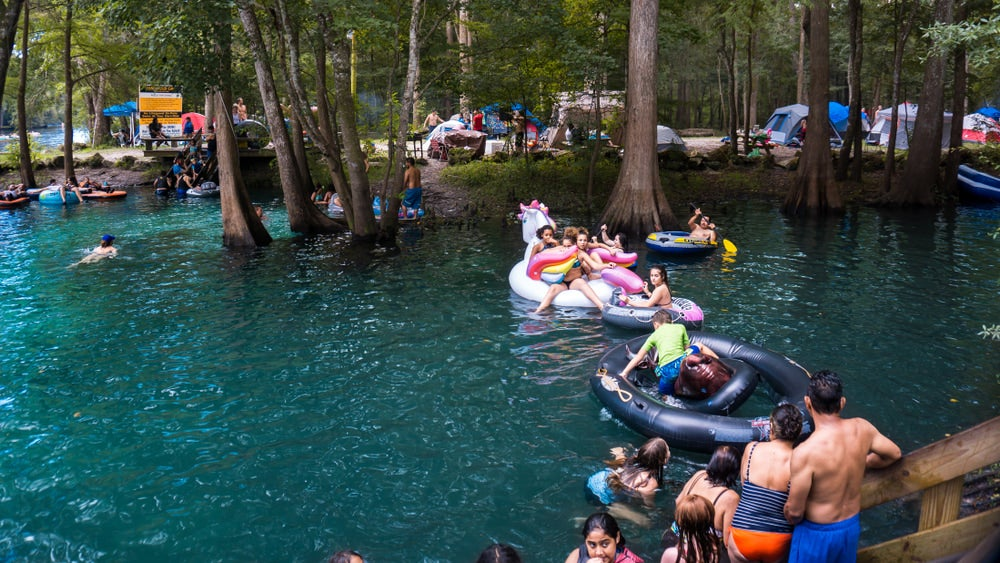 many people on inner tubes in a lake in florida near camping tent