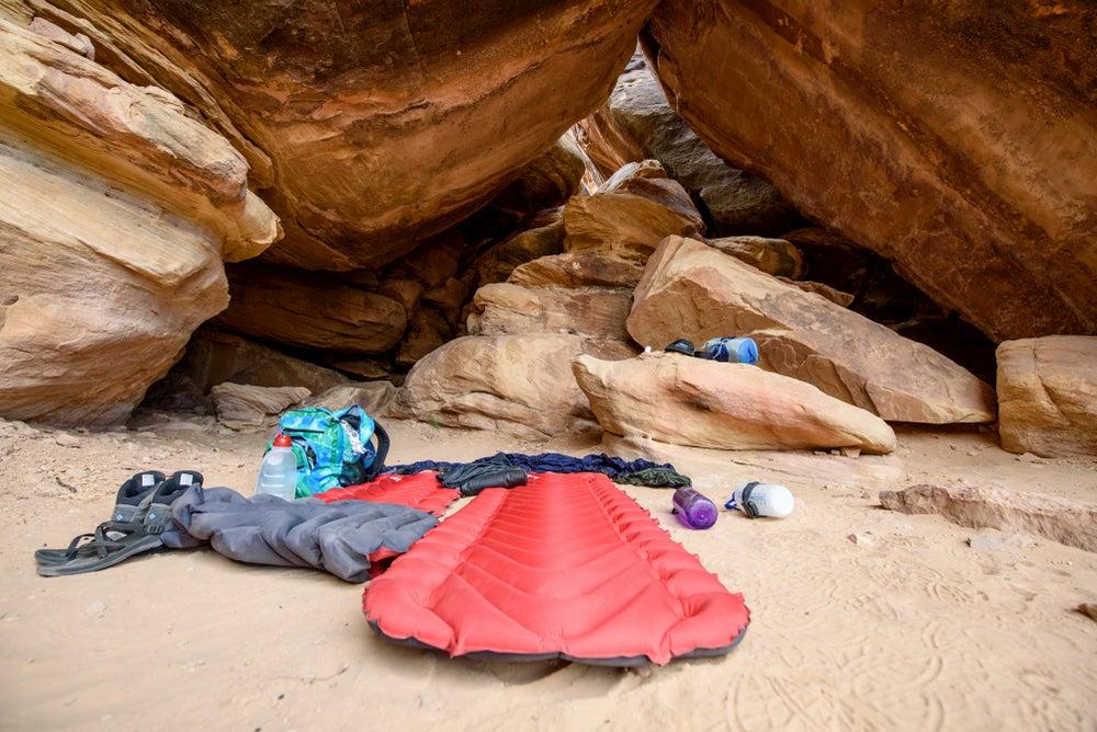 Sleeping pad and gear setup below rock formation.
