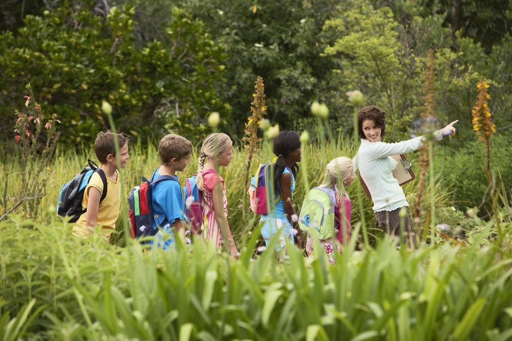 a woman leads a large group of kids in a field during school