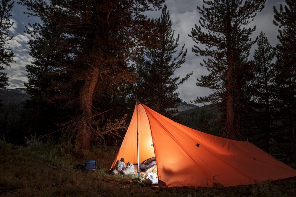 Orange tarp lit up at night in the backcountry.