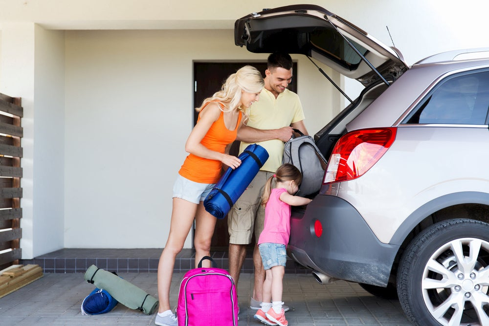 Family packing up car for a trip.