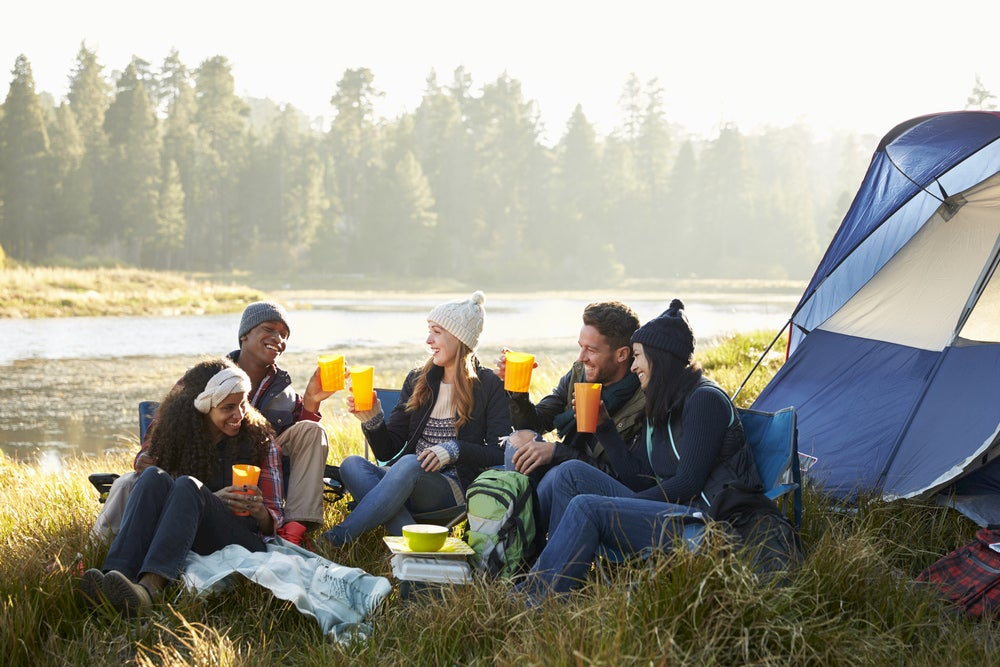 Group of friends hanging out beside a tent drinking out of plastic cups.