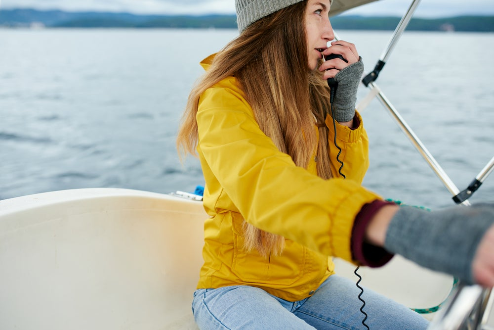 Woman steering a boat while talking into VHF radio.