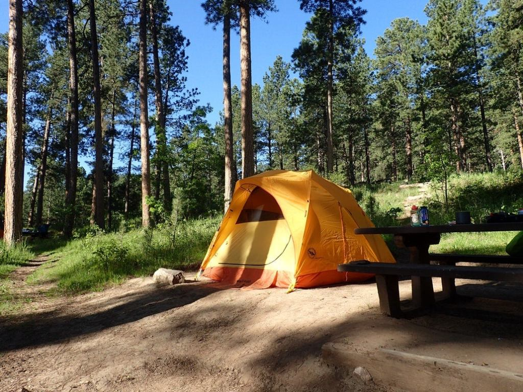 a yellow tent in a campsite in the woods