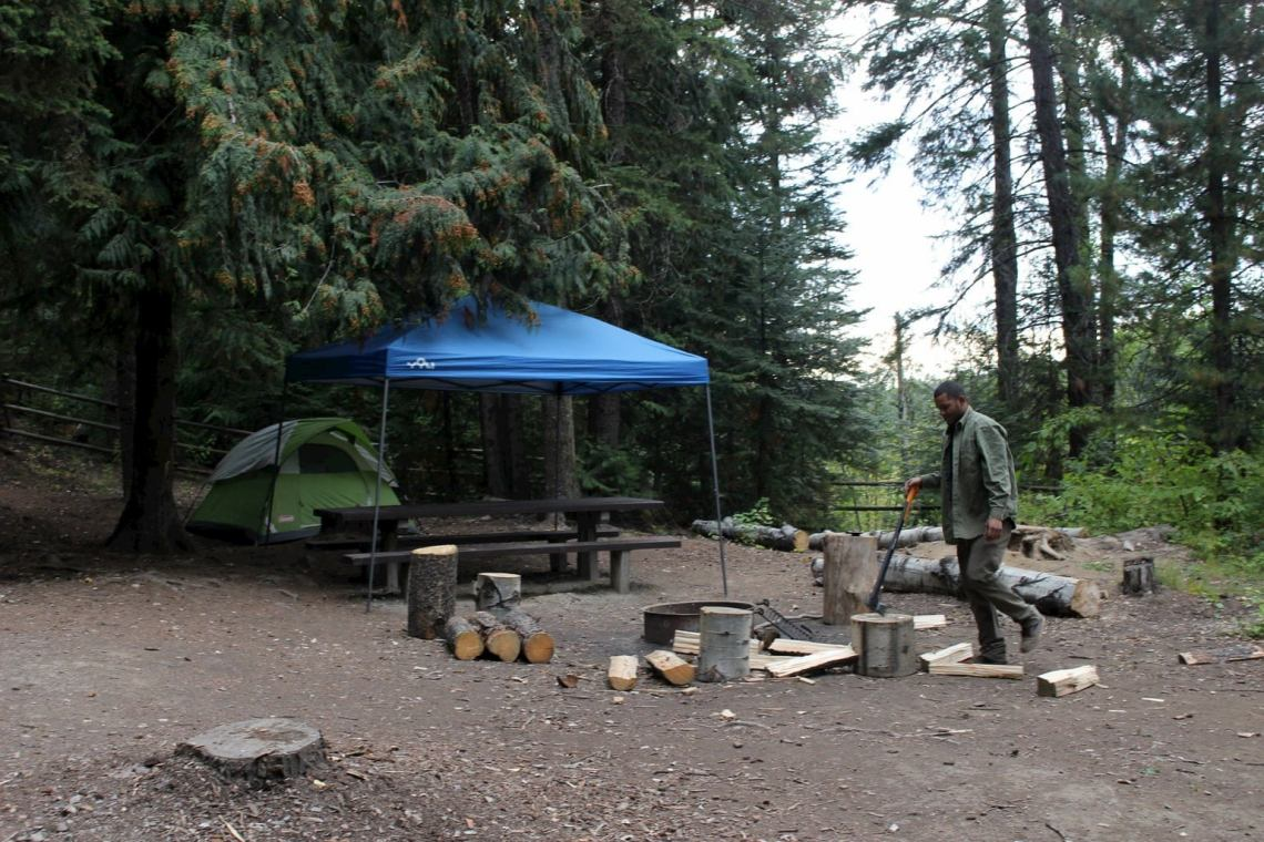 Camper chopping wood beside a fire pit at campsite.