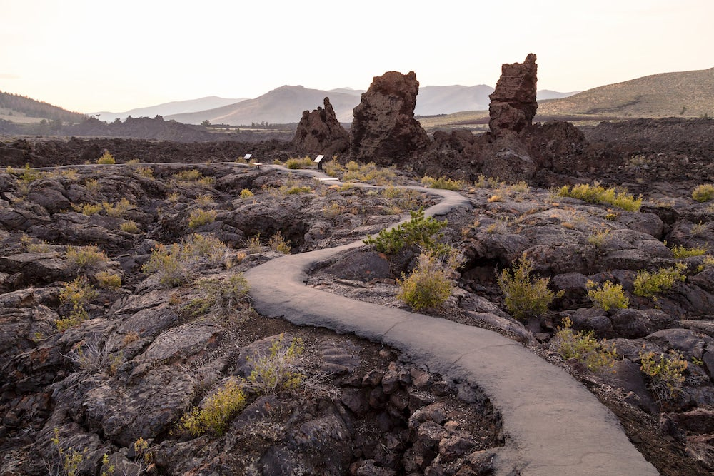 a paved trail winds around lava rocks in craters of the moon, idaho