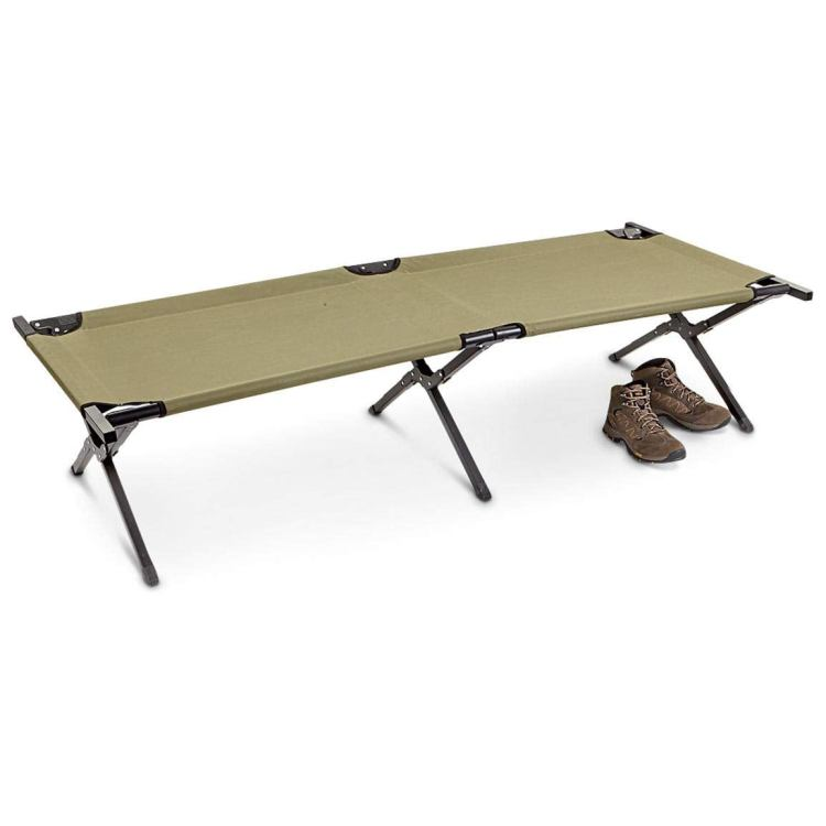 a green army cot with a pair of boots