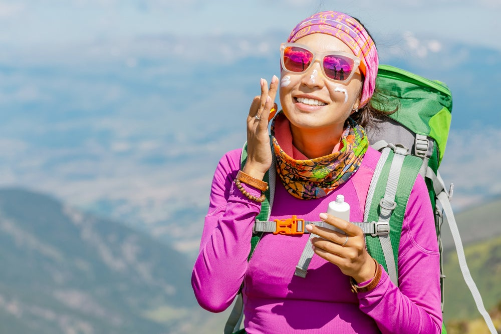 Female hiker applying sunscreen to her face.