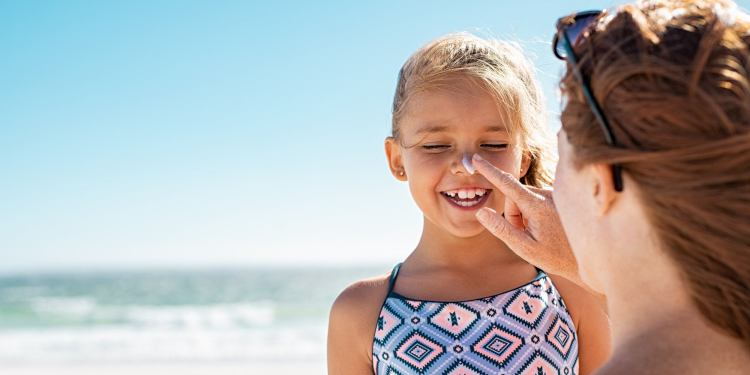 Mom applying sunscreen to her daughter's face on the beach.