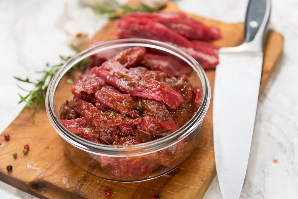 Meat with marinade in glass bowl on wood