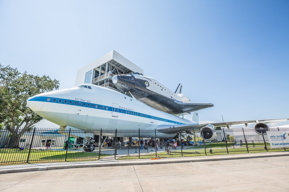 a space shuttle and a jumbo jet stacked outside the houston space center