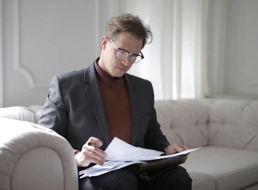 Um homem sentado analisando papeis.
