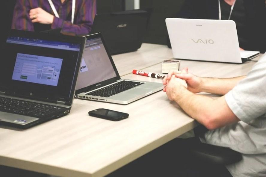 Pessoa concentrada no notebook sentada em uma mesa.